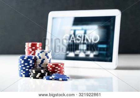 Online Gambling On Mobile Casino Concept. Stack Of Poker Chips And Tablet With Slot Machine On Scree