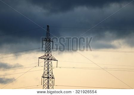 High Voltage Towers With Electrical Wires On Storm Sky Background. Electricity Transmission Lines, P