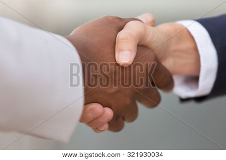 Closeup Of Diverse Business Colleagues Handshake. Multiethnic Business Partners Shaking Hands With E