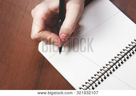 Woman Writing With Black Pen On Notebook