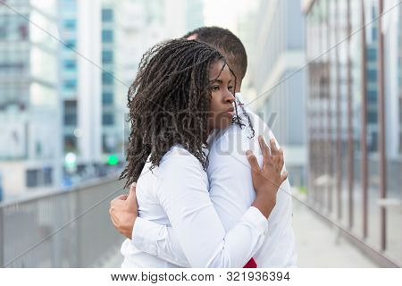 Young Couple Standing In City Street And Embracing Each Other. Diverse Close Friends Wearing Shite S