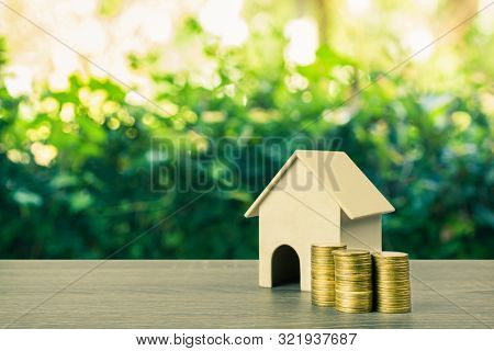 Property Investment, Home Loan, Reverse Mortgage Concept. A Small House Model With Stack Of Gold Coi