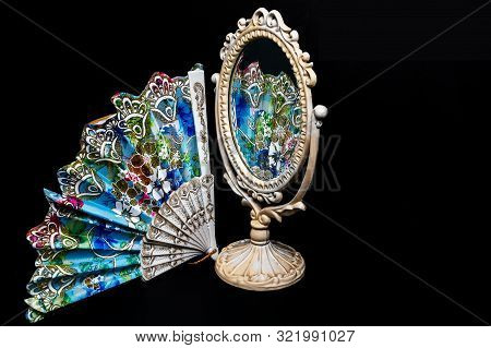 Colorful Hand Fan Reflects In Vintage Oval Desk Mirror With White Frame