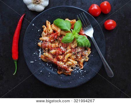 Pasta Arrabiata With Grated Pecorino Cheese On Dark Background.