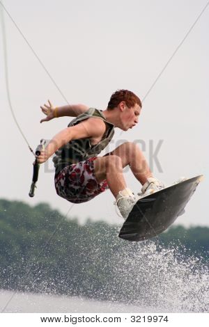 Teenage boy jumping high on the wakeboard poster