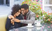Affectionate young african couple cuddling in cafe during date time, panorama with copy space poster