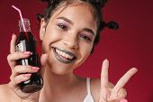 Image of cheerful punk girl with bizarre hairstyle and dark lipstick showing peace fingers while holding soda bottle isolated over red background poster