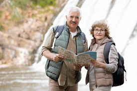 Happy senior couple with backpacks and map standing in front of camera with waterfalls behind while enjoying travel