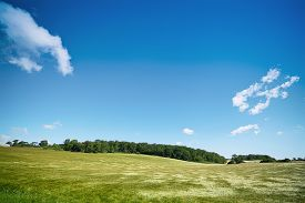 Rural Landscape With Fields Under A Blue Sky And A Green Forest In The Background