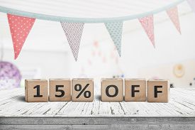 Special Price 15 Percent Off Promotion Sign On A Desk With Colorful Flags Above