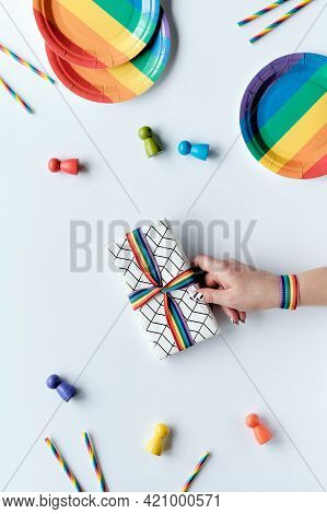 Lgbtq Community Pride Month Rainbow Concept Flat Lay. Hand With Rainbow Ribbon Holds Wrapped Gift. R