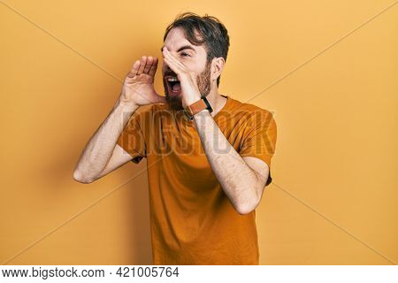 Caucasian man with beard wearing casual yellow t shirt shouting angry out loud with hands over mouth