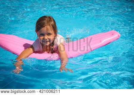 Happy Little Girl Swims And Plays In The Pool. Summer Vacation.