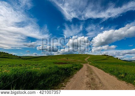 Wide Angle View, Dirt Road Leading To  The Top Of The Green Hill At Springtime, Beautiful Blue Sky W