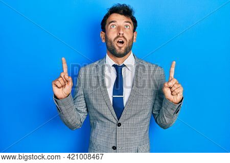 Handsome man with beard wearing business suit and tie amazed and surprised looking up and pointing with fingers and raised arms.