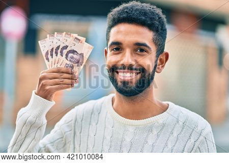 Young african american man smiling happy holding mexican 500 pesos banknotes at the city.