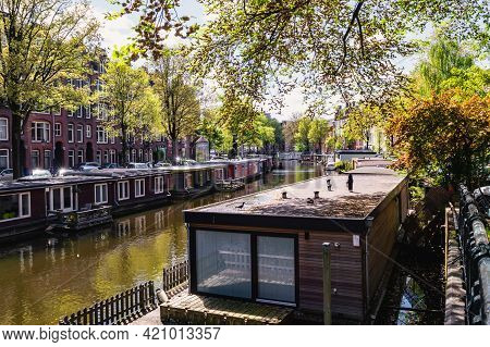 Amsterdam The Netherlands May 12, 2021 - An Amsterdam Canal Lined With Houseboats And Trees During T