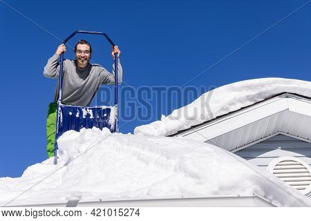 Wide Angle Views From Below Of A Young Man Posing With A Blue Manual Shovel From The Roof Of A House