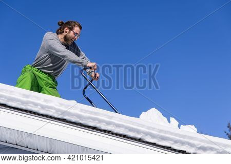 View From Below Of A Young Man Near The Edge Of The Roof Of A Snow Covered House, Removing Heaps Of