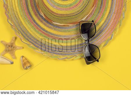 Summer Background. Striped Hat And Sunglasses On A Yellow Background. Summer Concept. Copy Space.