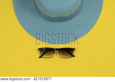 Summer Background. Blue Hat And Sunglasses Against Yellow Background. Top View, Close-up, Horizontal