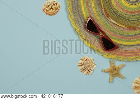 Summer Background. Striped Hat And Red Glasses On A Light Blue Background. Top View, Close-up, Horiz