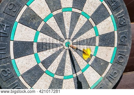 An Old Dart Board With A Dart In The Center.