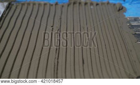 Process Of Laying Ceramic Tiles On Floor Smeared With Glue. Workers Hands With A Tile Close Up. The