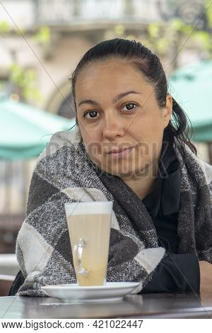 Street Portrait Of A 35-40-year-old Woman Sitting In A Blanket At A Table With A Cup Of Latte Coffee