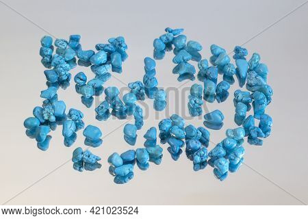 Turquoise Jewel Stones On Grey Mirror Background, Group Of Objects Front View