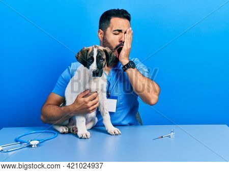 Handsome hispanic veterinary man with beard checking dog health yawning tired covering half face, eye and mouth with hand. face hurts in pain.
