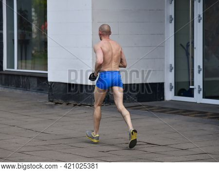 Elderly Man In Short Shorts Running Cross Country In The City In Cold Weather.
