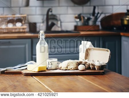Assorted Ingredients For Pastry Preparation Placed On Wooden Chopping Board On Table In Kitchen. Rus