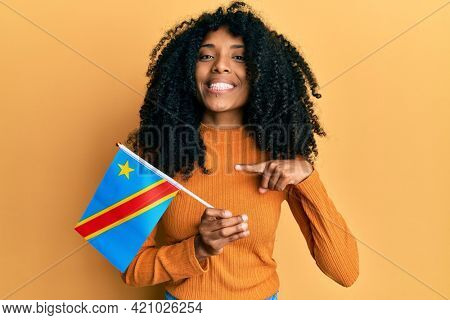 African american woman with afro hair holding democratic republic of the congo flag smiling happy pointing with hand and finger