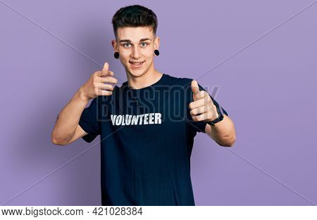 Young caucasian boy with ears dilation wearing volunteer t shirt pointing fingers to camera with happy and funny face. good energy and vibes.