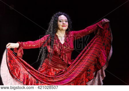 Gypsy Woman Barefoot With Long Black Hair Dances In A Red Dress On A Black Background. Horizontal Ph