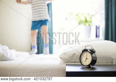 Just A Woken Up Little Child Jumping On The Bed With An Alarm Clock Standing On The Bedside Table In