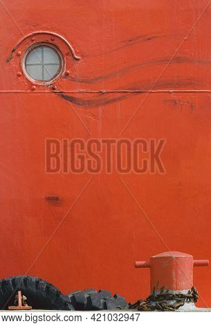 Porthole Window On Red Grunge Steel Hull Of Large Oil Tanker With Metal Mooring Bollard At Harbor In