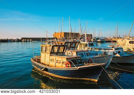 Venetian Fort Venetian fortress of Koules Castello a Mare castle in Heraklion and moored Greek fishing boats in port, Crete Island, Greece on sunset