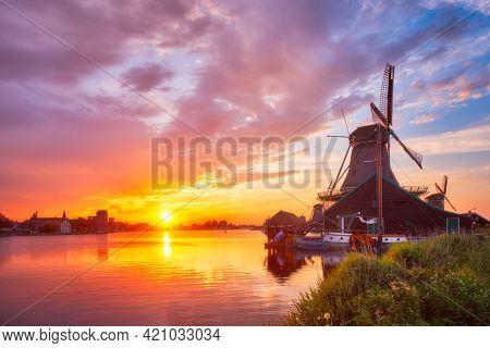 Netherlands rural scene - - windmills at famous tourist site Zaanse Schans in Holland on sunset with dramatic sky. Zaandam, Netherlands