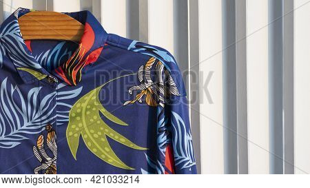 Part Of Colorful Short Sleeve Shirt In Blue Tone On Wooden Hanger Hang On White Plank Wall At Home