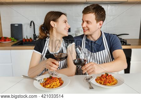 Happy Couple In Aprons Eating Bolognese Pasta With Wine At Modern Kitchen. Romantic Dinner At Home.