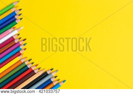 Colored Pencils Isolated On Yellow Background Close Up Concept With Copy Space For Text