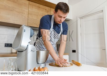 Young Handsome Man In Apron Kneading Dough In Modern Kitchen. Concept Of Homemade Bakery Food, Male