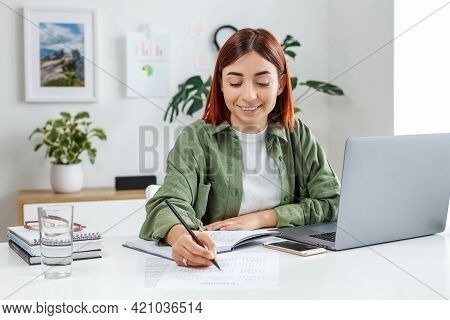 Woman Remotely Working At Home With Laptop Computer. Young Businesswoman Planning Her Time. Concept