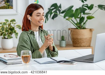 Woman Remotely Working At Home With Laptop. Young Businesswoman Talking Via Wireless Earphones. Conc