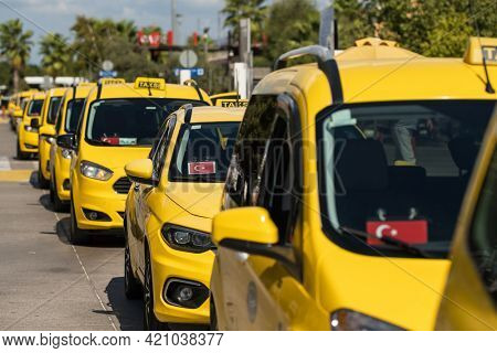 Line of taxi service cars waiting for passengers in airport in Turkey. Taxi signs in turkish on the cars