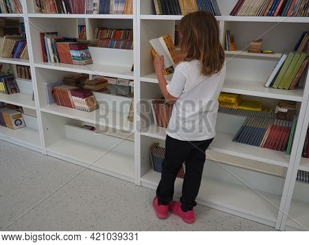 Sremska Mitrovica, Serbia May 15, 2021. A 7-year-old Girl In A White T-shirt Stands Near The Bookshe