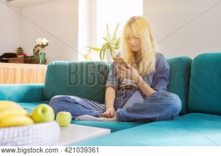 Smiling Happy Female Teenager Sitting At Home On Couch Looking At Smartphone Screen