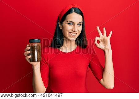 Young hispanic woman holding soluble coffee doing ok sign with fingers, smiling friendly gesturing excellent symbol